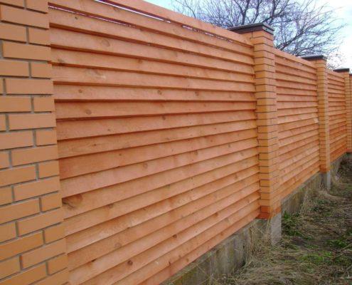 деревянный забор с кирпичными колоннами