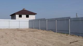 серый забор на строящийся участок